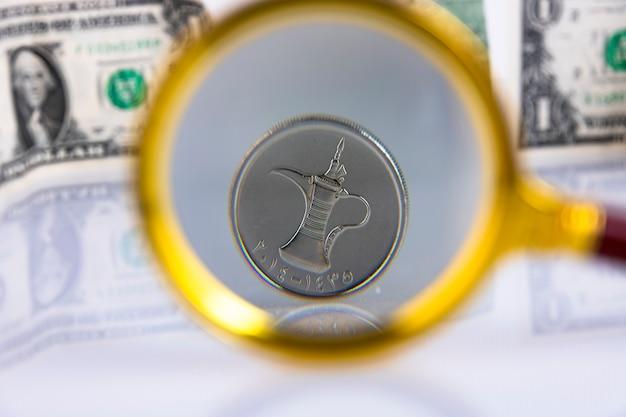 アラブ首長国連邦の通貨ディルハムコイン、米ドルを背景に虫眼鏡を通して表示します。スペースをコピーします。