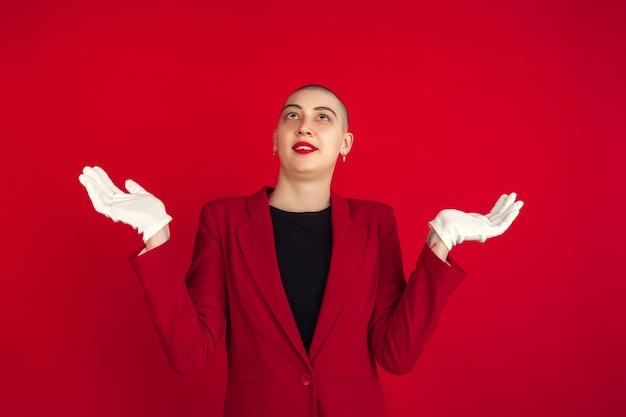 확실성, 묻는다. 빨간 스튜디오 벽에 격리된 젊은 백인 대머리 여성의 초상화.