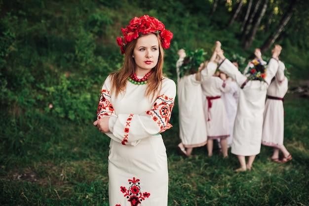 Юная девушка в традиционной одежде и цветочном венке