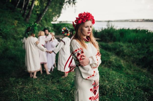 Юная девушка в традиционном платье и венок из роз