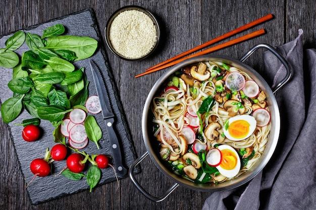 だし屋のだし、醤油、みりんをベースにしたうどん麺スープアジア料理、ほうれん草、大根、やわらかいゆで卵、きのこスライスを鍋に箸と具材で添えて、上面図、