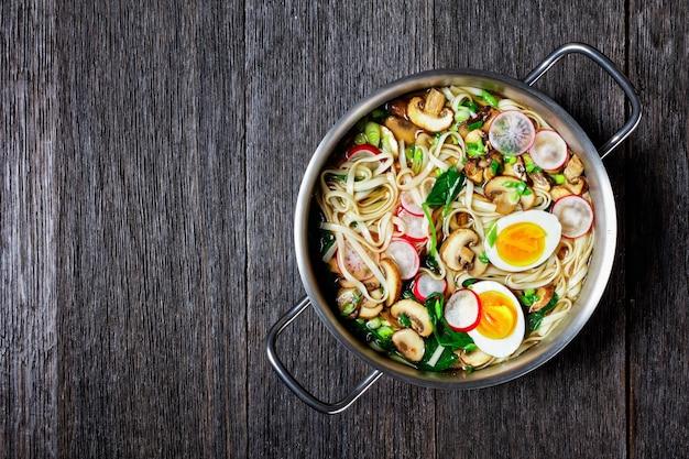 うどんスープ-ほうれん草、大根、やわらかいゆで卵、スライスしたキノコを濃い色の木製の背景に鍋に盛り付けたうどんの温かい和風スープ、上面図、コピースペース