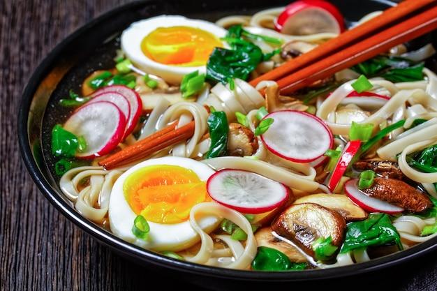 우동 국수 - 시든 시금치, 무, 부드러운 삶은 달걀, 어두운 나무 배경에 얇게 썬 버섯, 위쪽 전망, 클로즈업