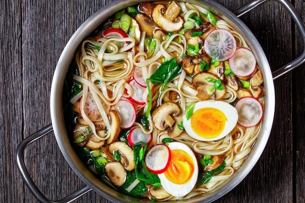 うどんスープ-ほうれん草、大根、やわらかいゆで卵、濃い木の背景の鍋にスライスしたキノコを添えたスープのうどんの金属鍋、上面図、クローズアップ