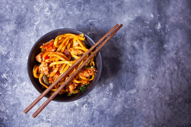Udon noodles with chicken meat in bowl on dark stone background. top view.