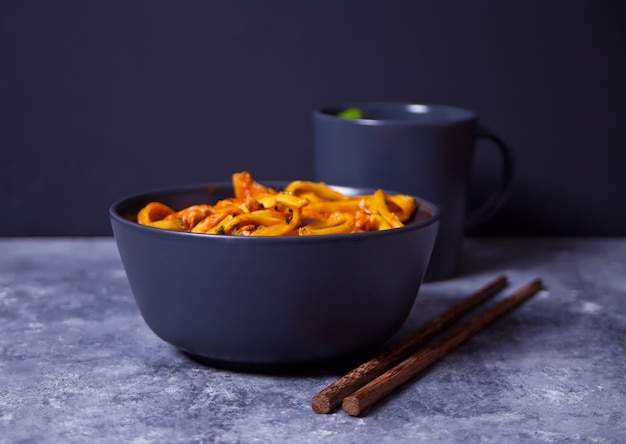 Udon noodles with chicken meat in bowl on dark stone background.