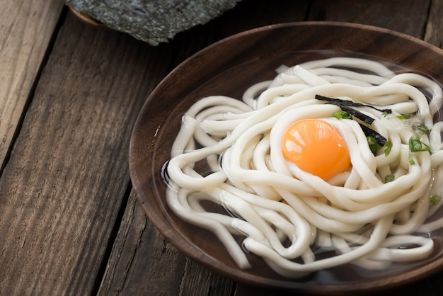 Udon noodles with law egg on wood plate