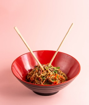 Udon noodles with meat bell pepper carrot spring onion soy sauce and sesame in a bowl
