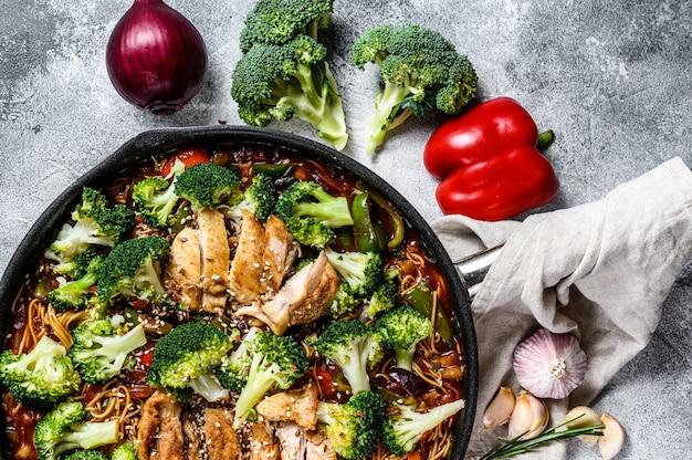 Удон жарит лапшу с курицей на сковороде. серый фон вид сверху