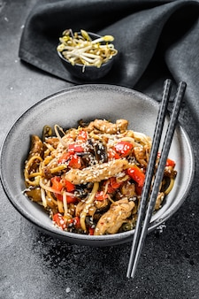 Udon stir-fry noodles with chicken meat and sesame on black