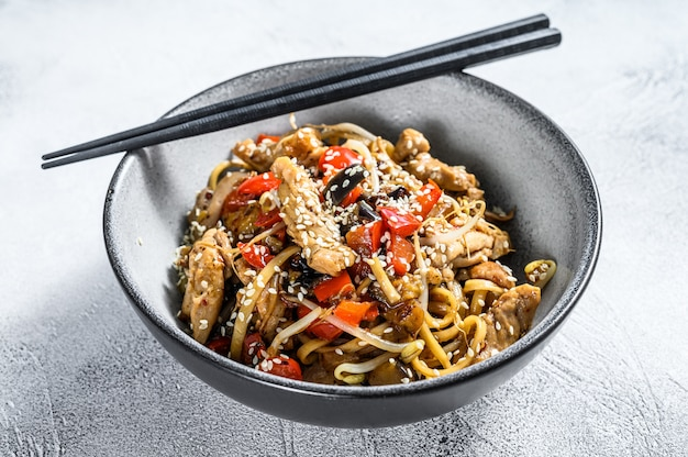 Udon stir-fry noodles with chicken meat and sesame on gray. top view