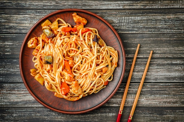 Udon stir-fry noodles with chicken and sweet and sour sauce and wooden sticks on wooden table