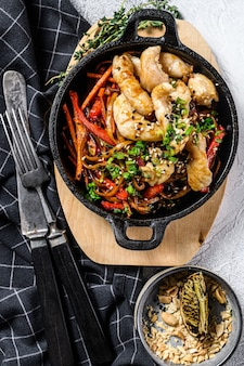 Udon stir fry noodles with chicken and vegetables in pan