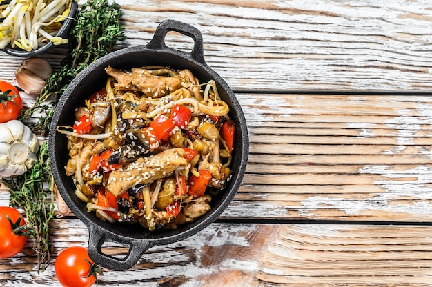 Udon stir fry noodles with chicken and vegetables in a pan