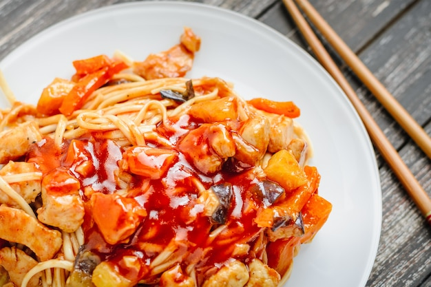 Udon stir fry noodles with chicken and vegetables in plate and chopsticks on black wooden background