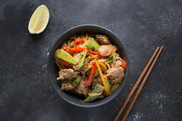 검은 그릇에 돼지 고기와 야채가 들어간 우동 볶음 국수. 아시아 요리.