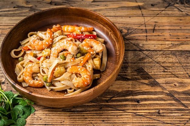 Udon stir-fry noodles with shrimp prawns in a wooden bowl. wooden