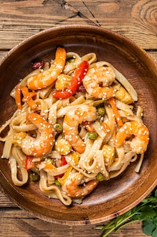 Udon stir-fry noodles with shrimp prawns in a wooden bowl
