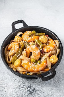 Udon stir-fry noodles with shrimps prawns in a pan. white background. top view.