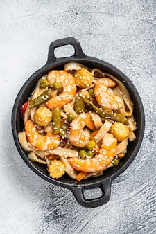 Udon stir-fry noodles with shrimps prawns in a pan. white