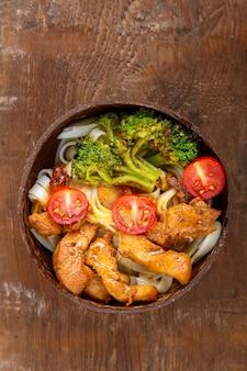 나무 탁자에 있는 코코넛 껍질 접시에 일본 소스를 얹은 우동