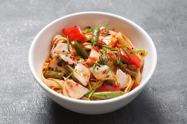 Udon with chicken and vegetables in sweet and sour sauce