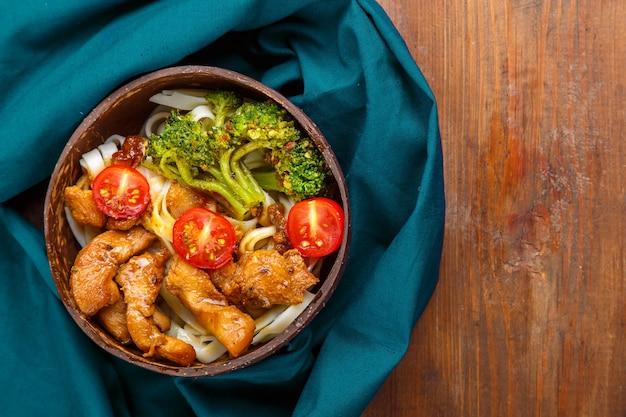 블루 냅킨에 나무 테이블에 코코넛 껍질 접시에 야키니쿠 소스에 고기와 야채를 넣은 우동. 가로 사진