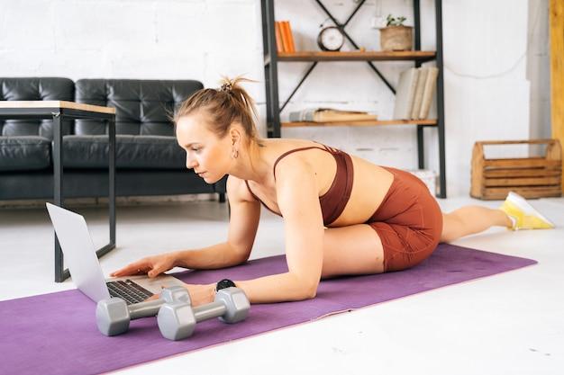 ウファ、ロシア-2020年5月15日。トレーニングトレーニング中にラップトップでオンライン運動を見ているスポーツウェアを身に着けている完璧な運動体を持つ魅力的なフィットの若い女性。健康的なライフスタイルの概念