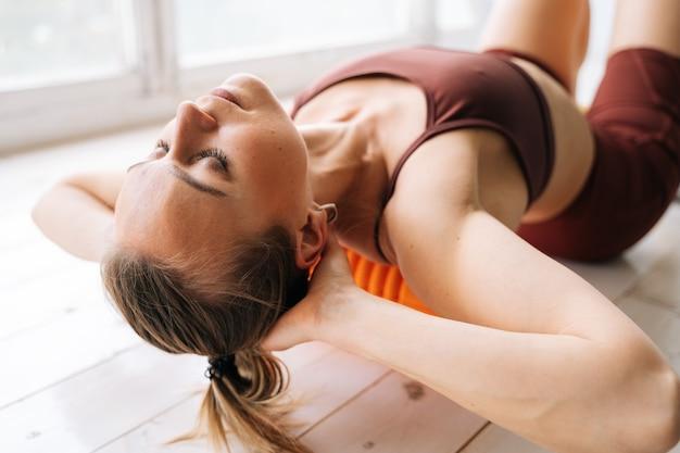 Ufa、ロシア-2020年5月15日。背中の高い筋肉の筋膜をマッサージし、マッサージローラーの窓枠で仰向けに横たわっている完璧な運動体を持つフィットした若い女性のクローズアップ顔。