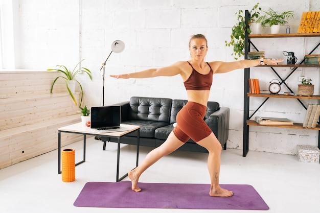 Ufa、ロシア-2020年5月15日。運動マットの上に裸足で立って運動をしているスポーツウェアを身に着けている完璧な運動体を持つ筋肉にフィットする若い女性。健康的なライフスタイルと活動の概念