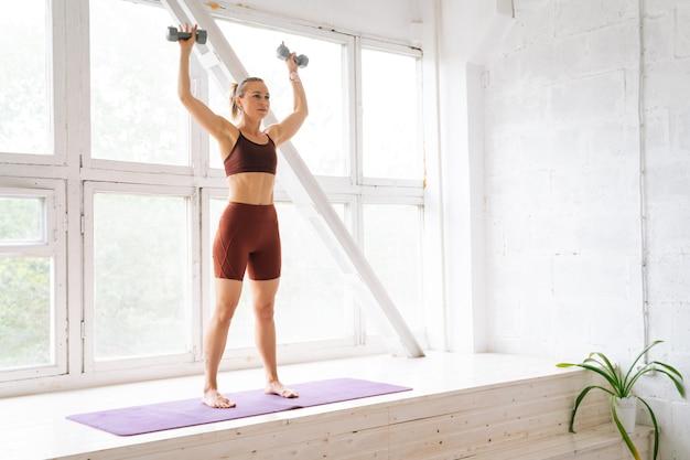 Ufa、ロシア-2020年5月15日。トレーニング中に窓枠に立っているバーベルで手を上げるスポーツウェアを身に着けている完璧な運動体を持つ筋肉にフィットする若い女性。健康的なライフスタイルの概念
