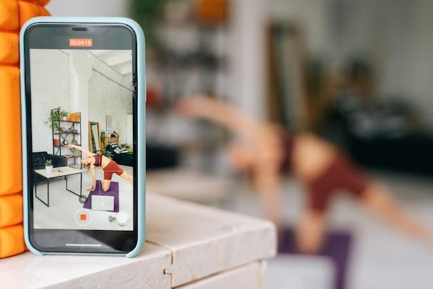 Ufa、ロシア-2020年5月15日。ラップトップでオンラインストリームを見て、床で運動しているスポーツウェアを身に着けている完璧な運動体を持つフィットの若い女性の電話画面ビュー。健康的なライフスタイルの概念