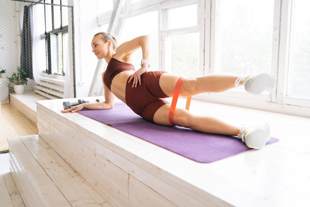 ウファ、ロシア-2020年5月15日。窓枠のエクササイズマットの上でサイドプランクポーズをし、目をそらしているスポーツウェアの完璧な運動体を持つかなり若い女性。健康的なライフスタイルの概念