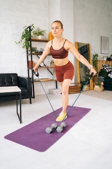Ufa、ロシア-2020年5月15日。運動マットに立っているストレッチラバーテープで運動するスポーツウェアを身に着けている完璧な運動体を持つスポーティフィットの若い女性。健康的なライフスタイルの概念
