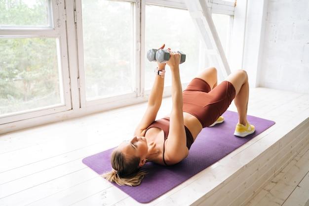 Ufa、ロシア-2020年5月15日。窓枠の運動マットの上に横たわっているダンベルで運動するスポーツウェアを身に着けている完璧な運動体を持つ強いフィットの若い女性。健康的なライフスタイルの概念