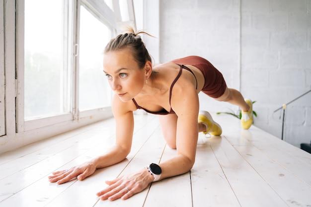 ウファ、ロシア-2020年5月15日。窓枠で脚のトレーニングをし、目をそらして、スポーツウェアを身に着けている完璧なアスリートの体を持つ強いフィットネスの若い女性。健康的なライフスタイルと身体活動の概念