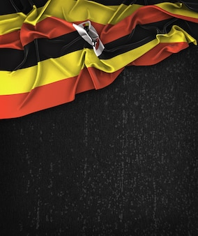 Uganda flag vintage on a grunge black chalkboard with space for text
