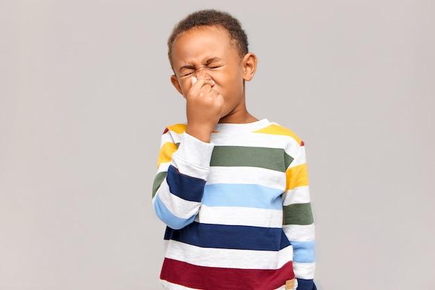 うーん、嫌な!悪臭や悪臭のために目を閉じて鼻をつまんでいる感情的な嫌悪感のあるアフリカ系アメリカ人の少年の肖像画。アレルギー、くしゃみをしている浅黒い肌の男児