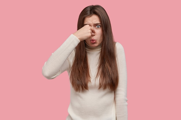 Ugh, what disgusting smell. discontent brunette woman covers nose, feels bad reek, wears casual white turtleneck sweater, notices rotten products