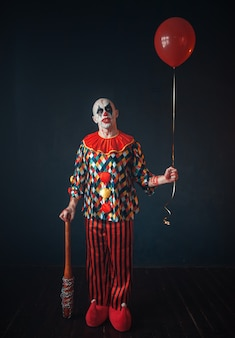 Ugly bloody clown with baseball bat and balloon