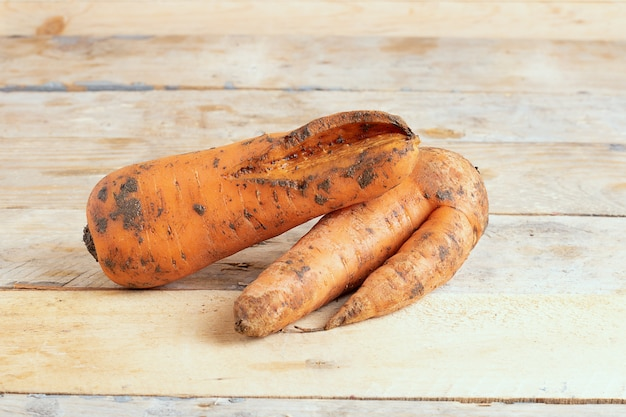 Уродливая кривая морковь на деревянном деревенском фоне.