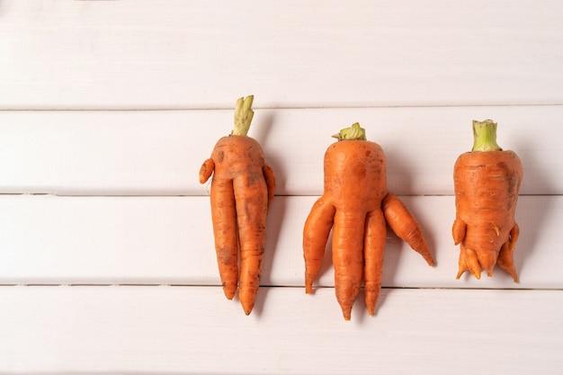 Уродливая изогнутая морковь на белом деревянном столе