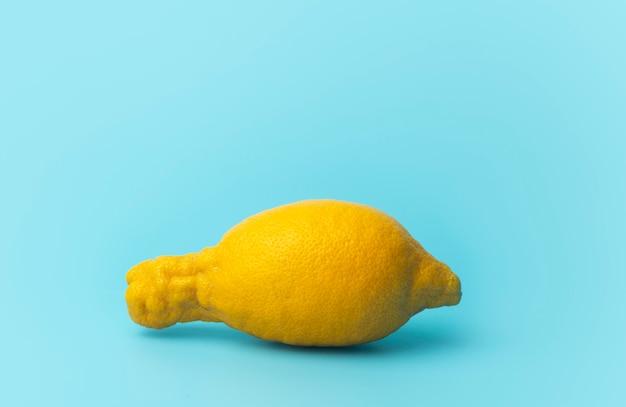 못생긴 음식과 못생긴 야채 개념입니다. 파란색 최소한의 배경에 못생긴 레몬입니다.