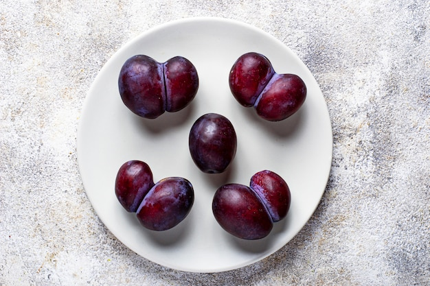 Ugly and normal plums, abnormal organic fruit
