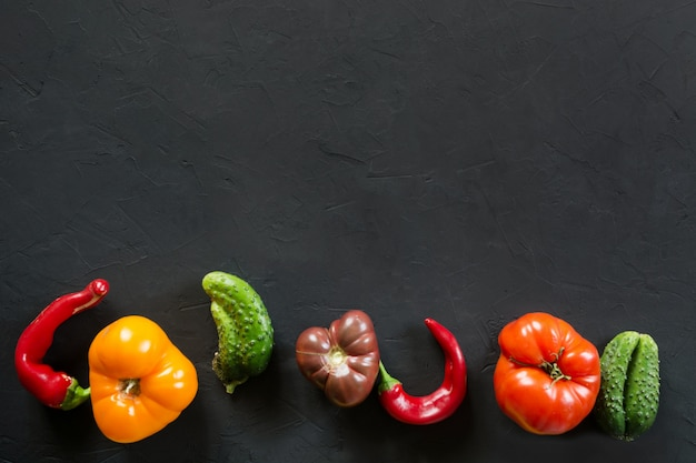 Ugly organic colorful tomato, pepper, cucumber on black,