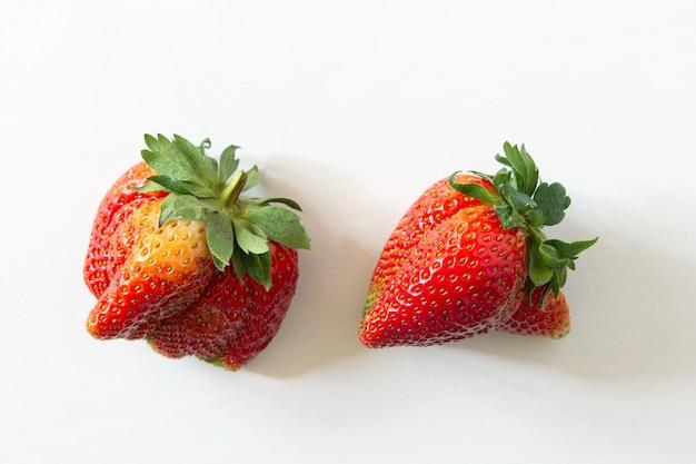 Ugly organic home grown strawberries on white wood