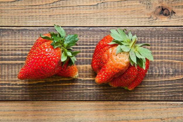 Ugly organic strawberries on wood