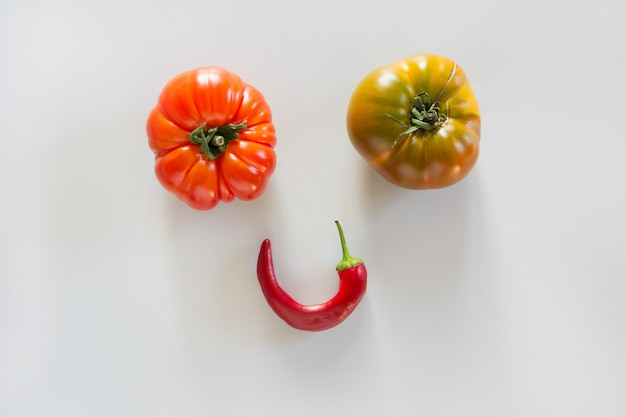 Ugly ripe tomatoes and pepper as face, smile with eyes.