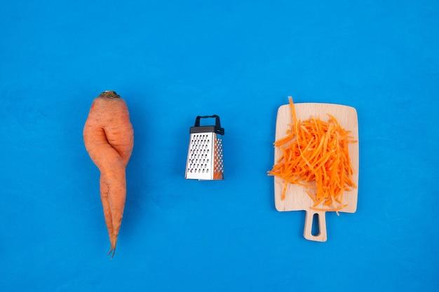 못생긴 야채. 파란색 배경에 강판 당근이있는 특이한 곡선, 이중 당근 및 강판. 파란색 배경, 복사 공간입니다. 개념-음식물 쓰레기 감소. 불완전한 제품 요리에 사용합니다.