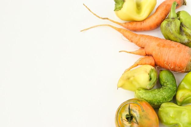 Уродливые овощи: морковь, огурец, перец и помидоры на белом фоне, концепция уродливой еды, горизонтальное фото, пространство для копирования